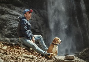 Man with dog sitting near waterfall